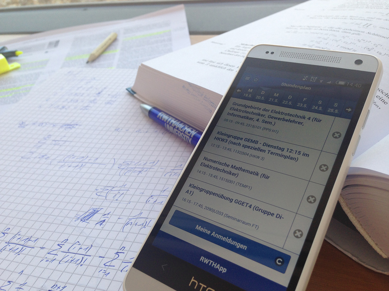 Photo of a mobile pphone with RWTH App and a book