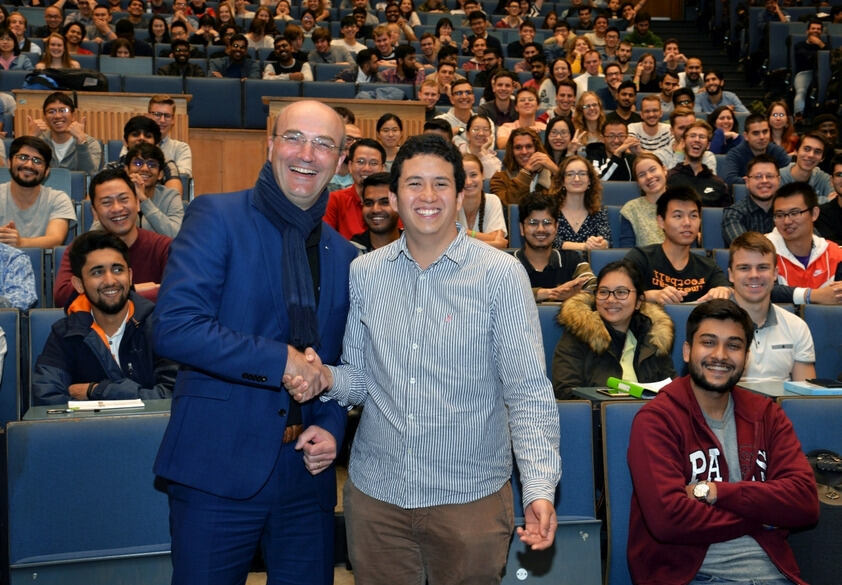 Rector Rüdiger shakes student's hand